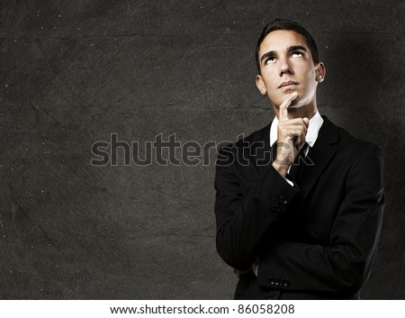 portrait of pensive young business man against a grunge background - stock photo