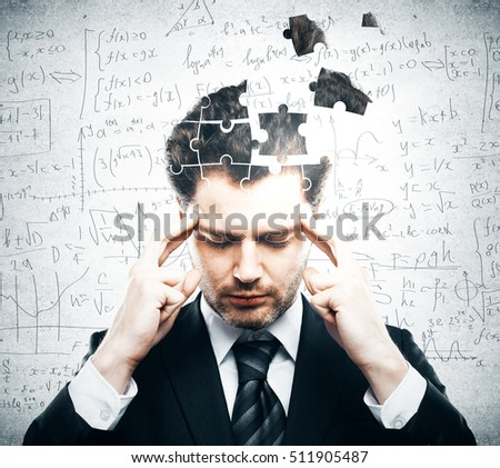 Portrait of pensive young businessman with puzzle piece head on grey background. Business challenge concept