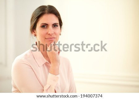 Portrait of pensive young businesswoman on pink blouse looking at you while standing on closeup background - copyspace - stock photo