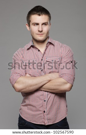 Portrait of pensive young handsome guy over gray background - stock photo