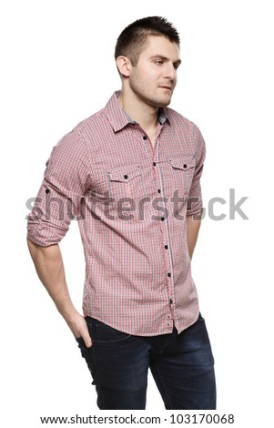 Portrait of pensive young man standing with his hands in pocket looking down, isolated on white background