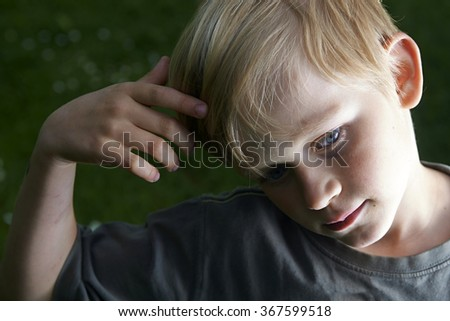 Portrait of pensive youngster (child blond boy) concentrated on something - stock photo