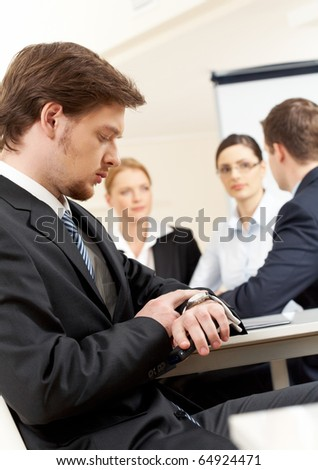 Portrait of people working with serious businessman in front looking at watch - stock photo