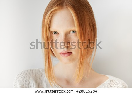 Portrait of perfect fresh and clean female face. Beautiful model woman with freckles and ginger hair looking at the camera. Youth and skin care concept. Isolated against white studio background - stock photo