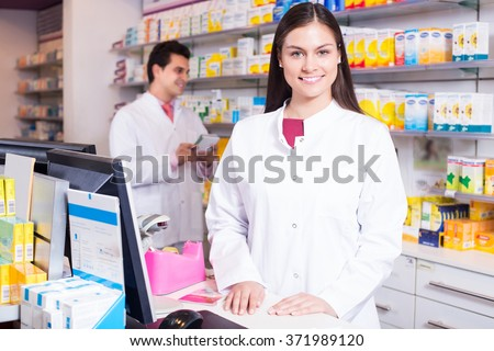 Portrait of pharmacist and assistant working at farmacy reception