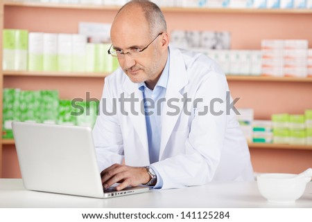 Portrait of pharmacist browsing the internet using laptop in drugstore - stock photo