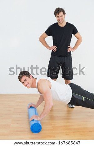 Portrait of physical therapist with young man doing push ups in the gym at hospital