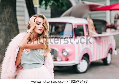 Portrait of pin up girl with pink fur stole on shoulder on retro car background. She has long blonde hair, keeps hand on head, looking down