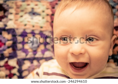 Portrait of playful baby with blue eyes - Candid image of young boy playing at home - stock photo