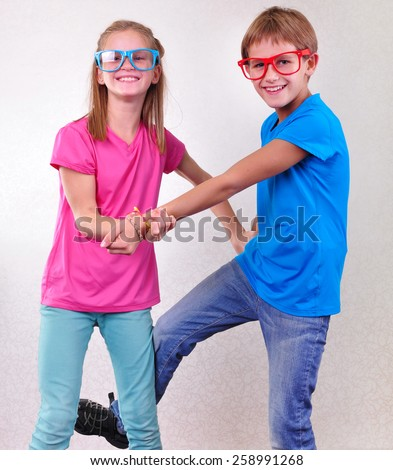 portrait of playful brother and sister twins with sunglasses fighting and having fun - stock photo