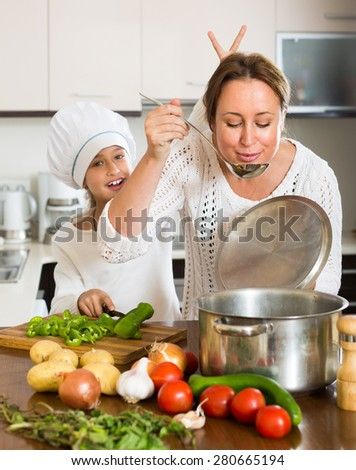Portrait of playful daughter and happy mom with vegetables and casserole at domestic kitchen. Focus on woman - stock photo