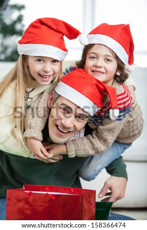 Portrait of playful father piggybacking children during Christmas at home - stock photo