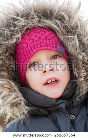 portrait of playful girl wearing fur hood looking at camera outdoor - stock photo