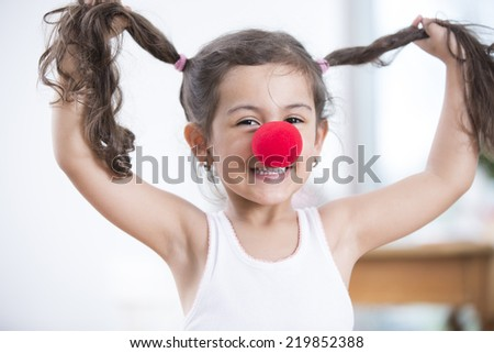 Portrait of playful little girl wearing clown nose holding pigtails at home - stock photo
