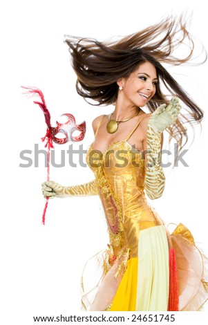 Portrait of playful woman in glamorous attire and mask in hand - stock photo