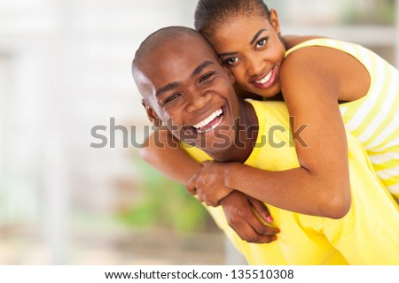 portrait of playful young african couple piggyback - stock photo