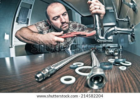portrait of plumber at work - stock photo