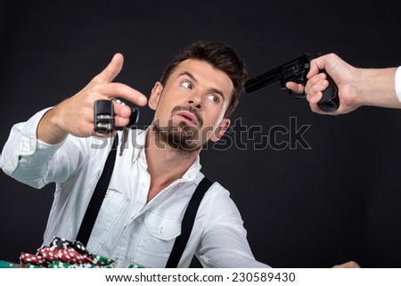 Portrait of poker player lost his car in the poker game. Someone threatening him weapons. - stock photo