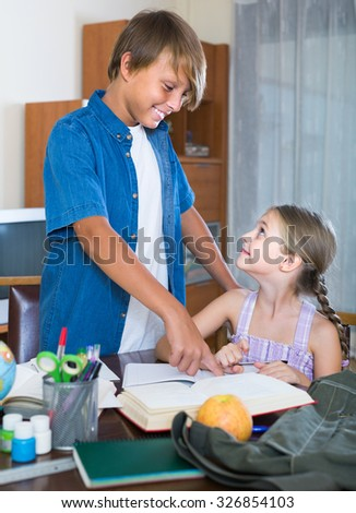 Portrait of positive american children with textbooks and notes in domestic interior