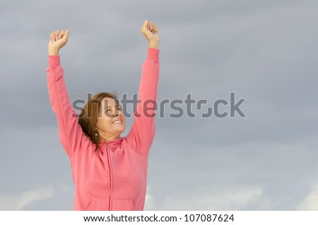 Portrait of positive and optimistic middle aged woman in winner pose outdoor at ocean, isolated with dark storm clouds as background and copy space. - stock photo