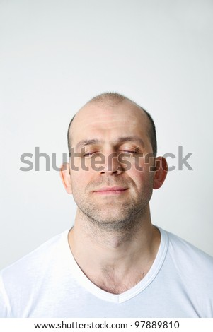 Portrait of positive bald-headed man with closed eyes on white background - stock photo