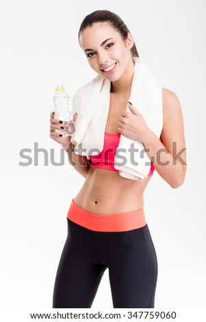 Portrait of positive charming fitness girl with white towel on her neck and bottle of water over white background