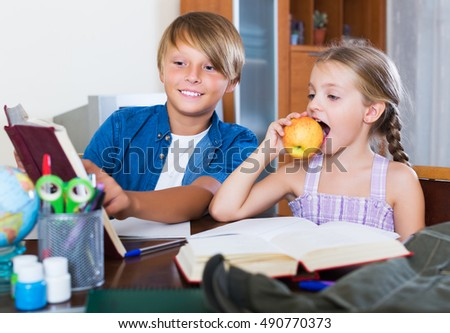 Portrait of positive children with textbooks and notes in livingroom
