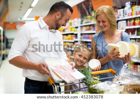 Portrait of positive family standing with full cart in supermarket. Focus on the girl