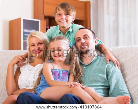 Portrait of positive family with two kids on couch indoors - stock photo