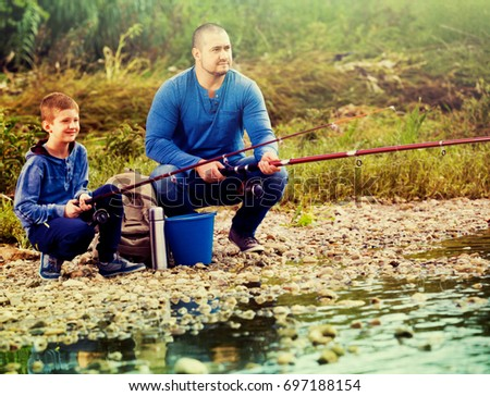 Portrait of positive  father and smiling son fishing with rods in summer day