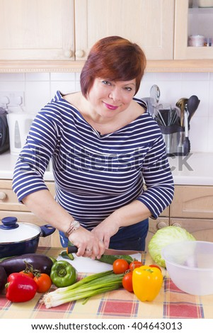 Portrait of positive female cooking healthy salad at kitchen