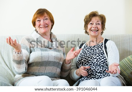 Portrait of positive female pensioners laughing in domestic interior - stock photo