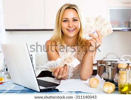 Portrait of positive girl with money and documents indoor