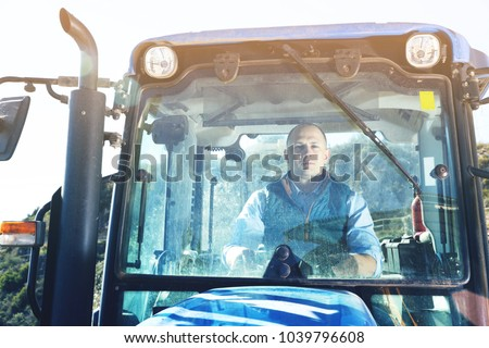 Portrait of  positive glad confident male owner of vineyard behind glass in tractor cab