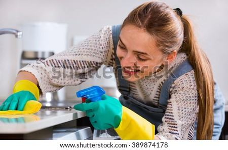 Portrait of positive housewife cleaning with supplies in kitchen
