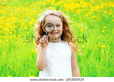 Portrait of positive little girl looking through a magnifying glass on summer floral yellow dandelions field - stock photo
