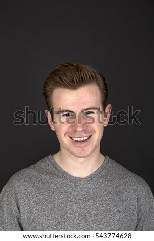portrait  of positive looking young man isolated on black