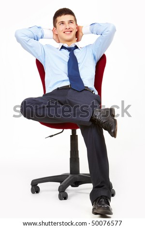 Portrait of positive man relaxing in arm-chair with hands behind head