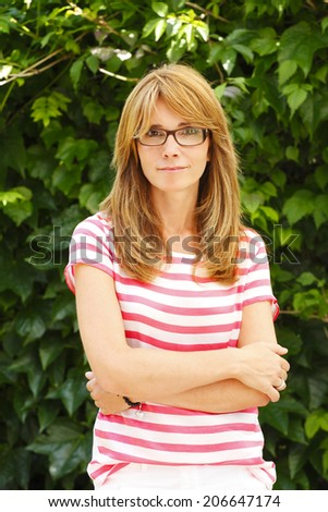 Portrait of positive mature woman standing. - stock photo