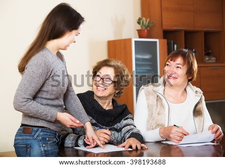 Portrait of positive mature women with papers and agency employee - stock photo