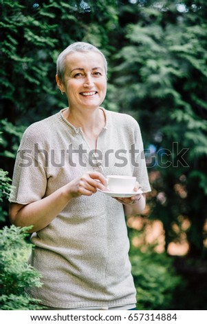 Portrait of positive middle aged woman with short gray hair drinking and holding white cup of tea in sunny morning over green tree background.