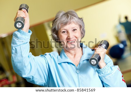 Portrait of positive senior woman lifting dumbbells, looking at camera and smiling - stock photo