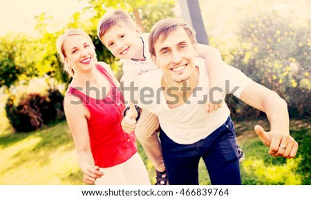 Portrait of positive smiling family with boy sitting on father's back hugging each other in park