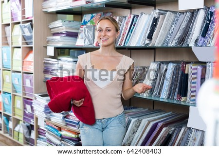 Portrait of positive woman choosing blanket in bedding section in shop