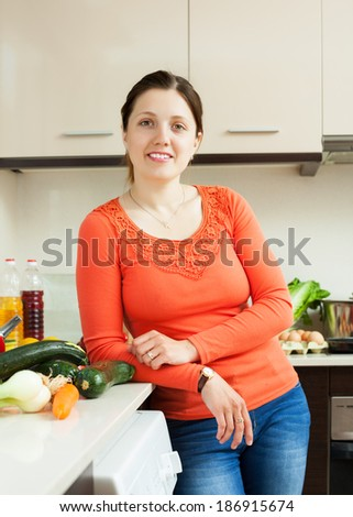 Portrait of positive  woman in home kitchen