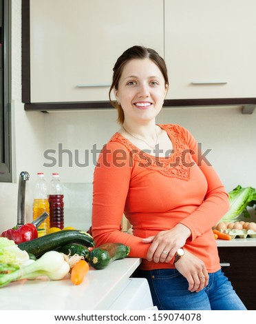 Portrait of positive  woman with fresh vegetables in home kitchen
