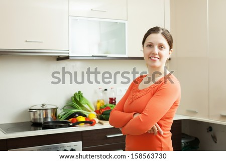 Portrait of positive woman with vegetable marrow in domestic kitchen
