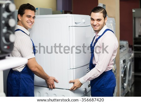 Portrait of positive workers in uniform working at household appliances store - stock photo
