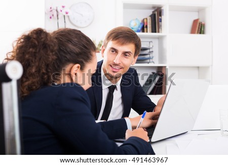 Portrait of positive young business man sitting with laptop on desk in office on working day