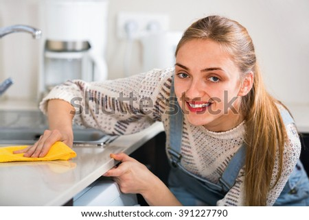Portrait of positive young housewife cleaning with supplies in kitchen - stock photo